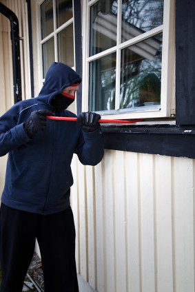 A person breaking into a home via the window.