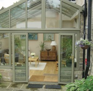 Green conservatory with french doors open.