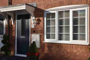Black composite door and white double glazed window on red brick house.