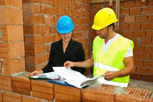 Two people looking at planning and building regulations on site.