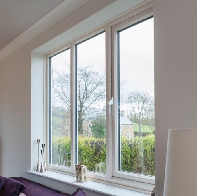 White casement window looking onto a garden.
