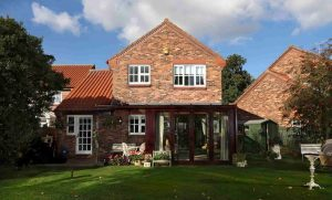 A beautiful red brick home with a dark brown conservatory.