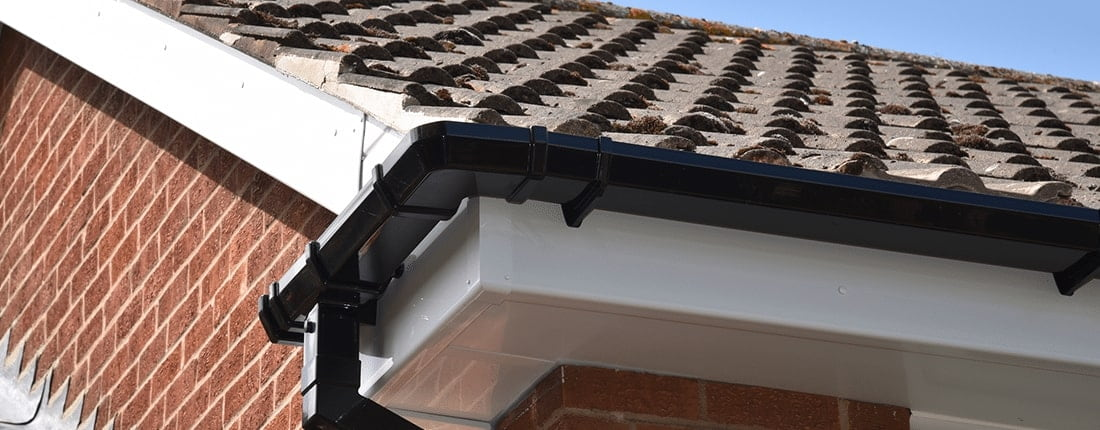 A close up shot of the corner of the black gutting on a roof.