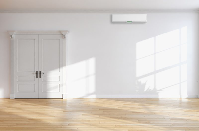 A white door in a white walled room.