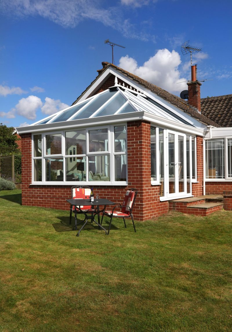 A red brick conservatory with white windows.