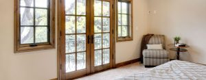 Wooden French doors and windows in a cream bedroom.