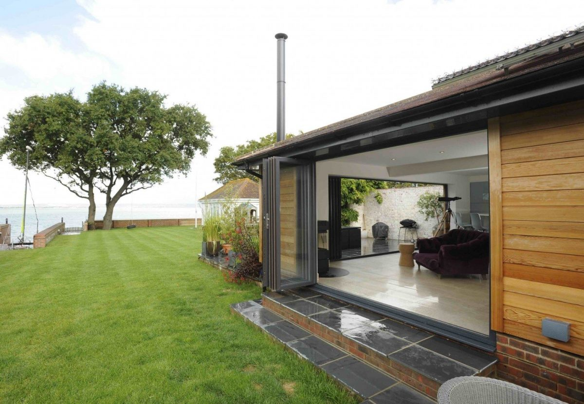Bifold doors open at a home near the sea.