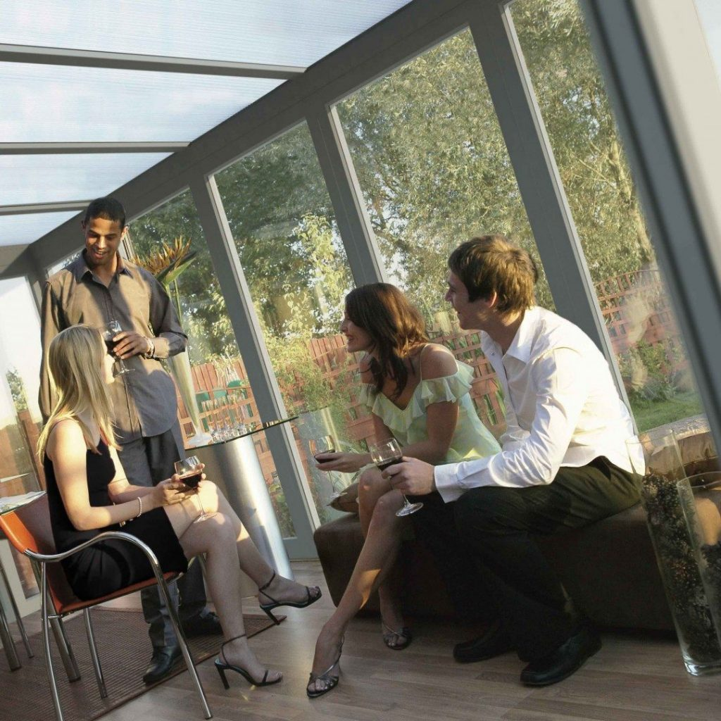 Friends socialising inside a conservatory.