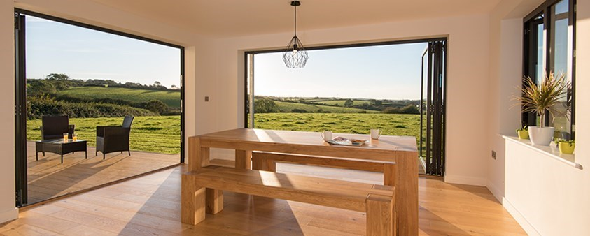 Looking out on fields from two retracted bifold doors.