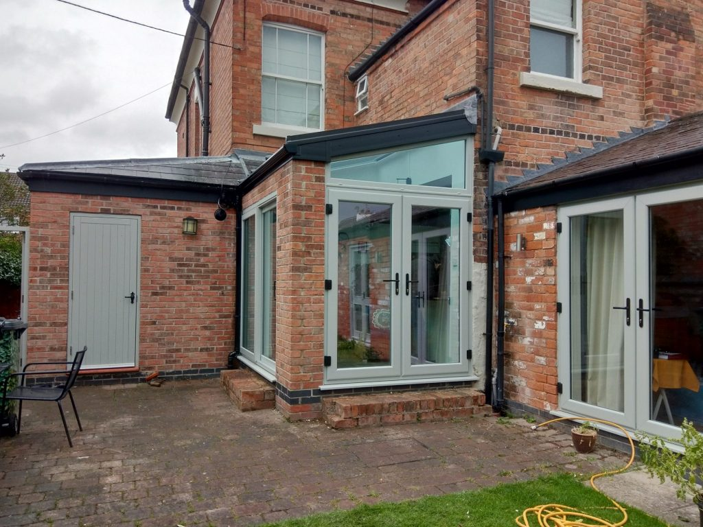 A wonderful gray Conservatory with matching windows and side door on a red brick house.