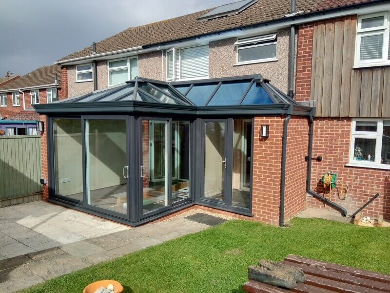 Black conservatory with glass roof.