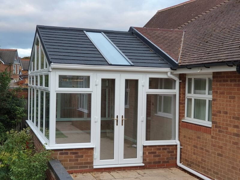 A black tiled roof on a red brick conservatory.