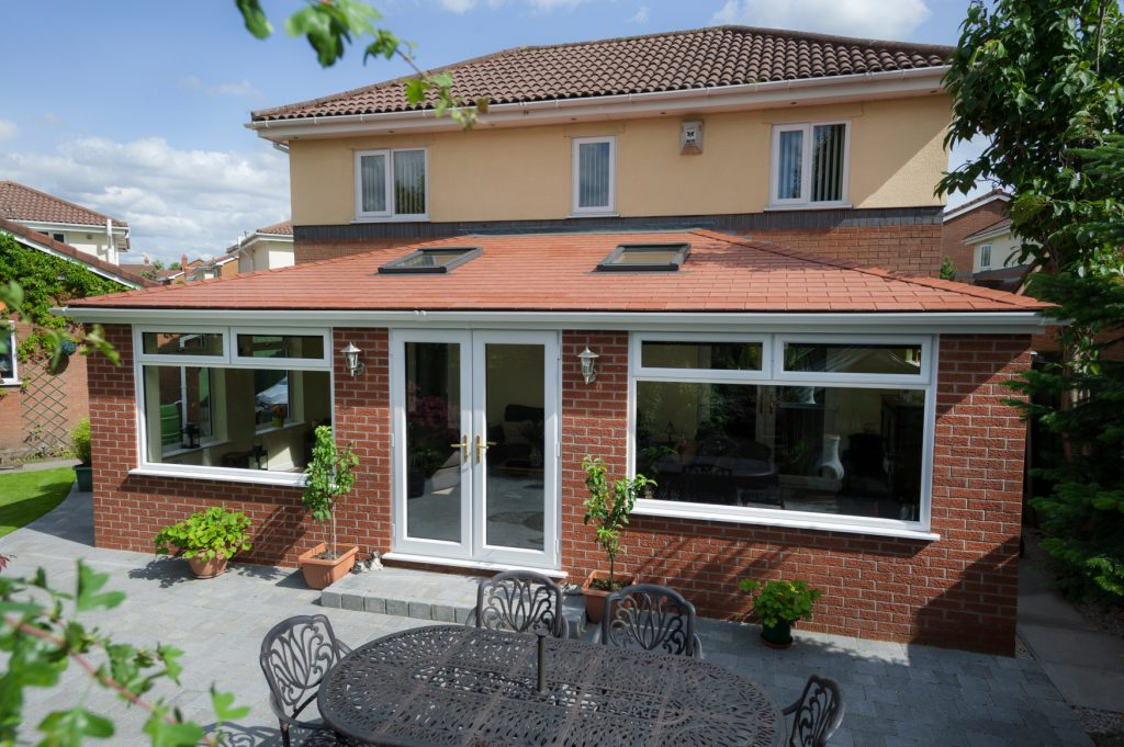 A Solid Roof Conservatory in White Exterior with Red Tile Roof.