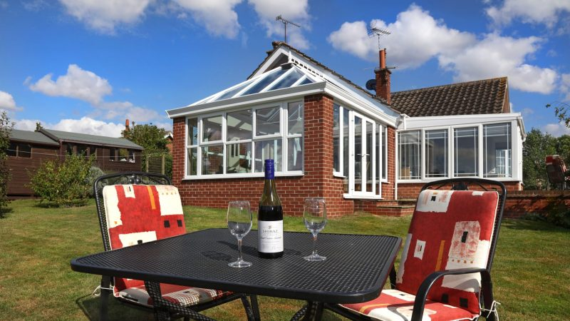 Outside white uPVC orangery with a glass of wine on a table.