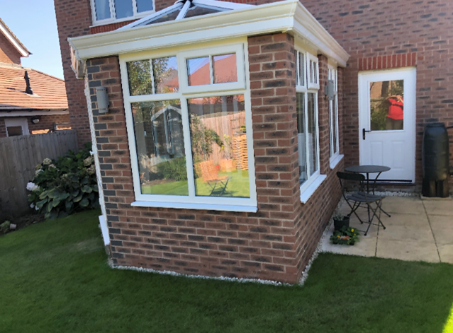 White windows and roof on a modern brick conservatory.
